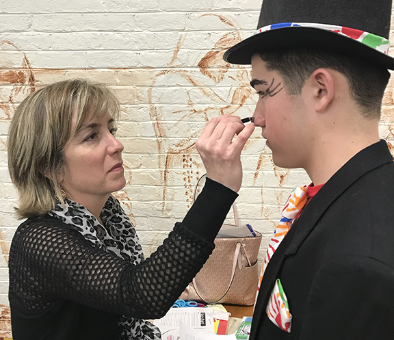 A parent volunteer helps with makeup for