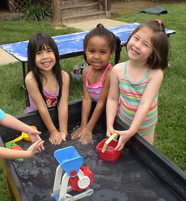 Three preschool girls playing at the water table on Sprinkler Day