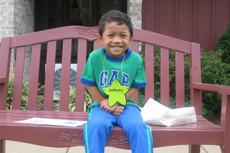 Student smiling, sitting on bench, on first day of preschool