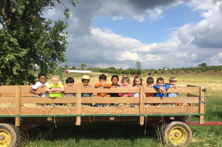 Preschoolers in a hay wagon with heart-shaped cloud above